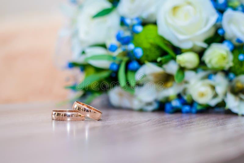 Alianças de casamento na tabela ao lado do ramalhete fotos de stock royalty free