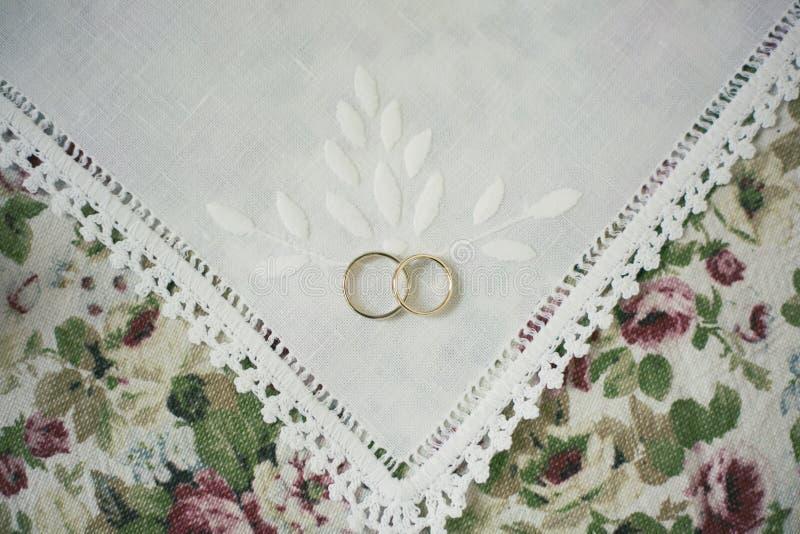 Alianças de casamento na toalha de mesa branca imagens de stock royalty free
