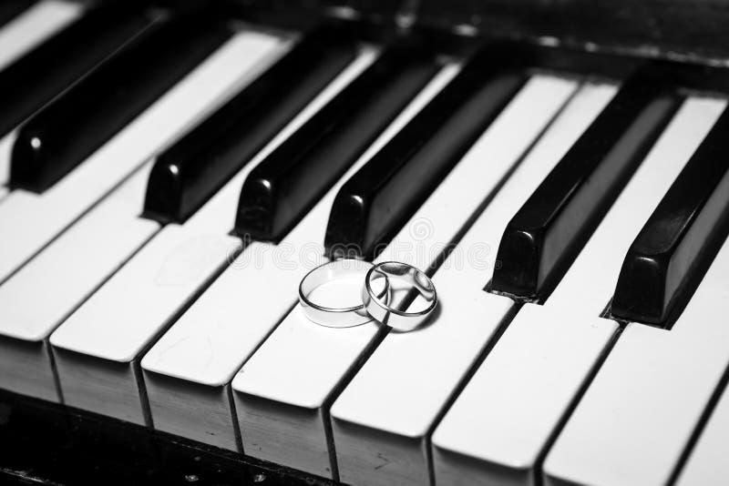 Alianças de casamento no piano foto de stock royalty free