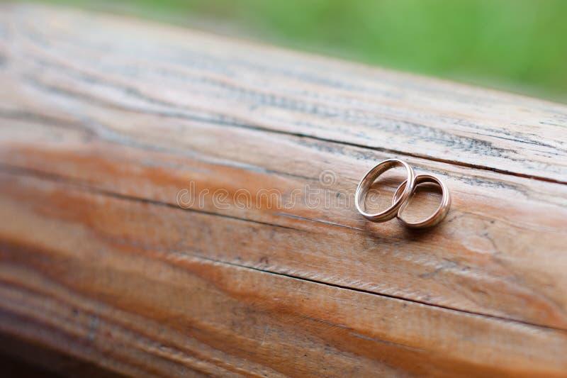 Alian?as de casamento em uma textura de madeira clara Joia do casamento fotos de stock royalty free