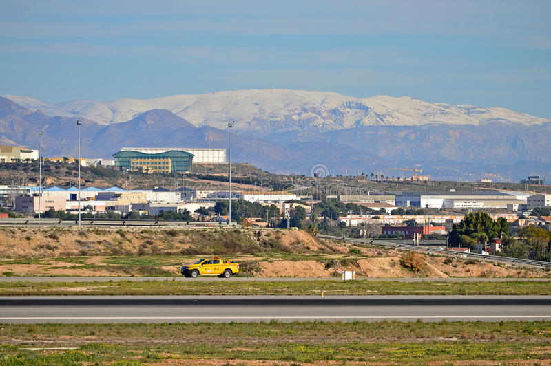 Alicante Airport Under The Snow. An airport car is used to check the runway for debris with highly unusual snowy conditions stock photography