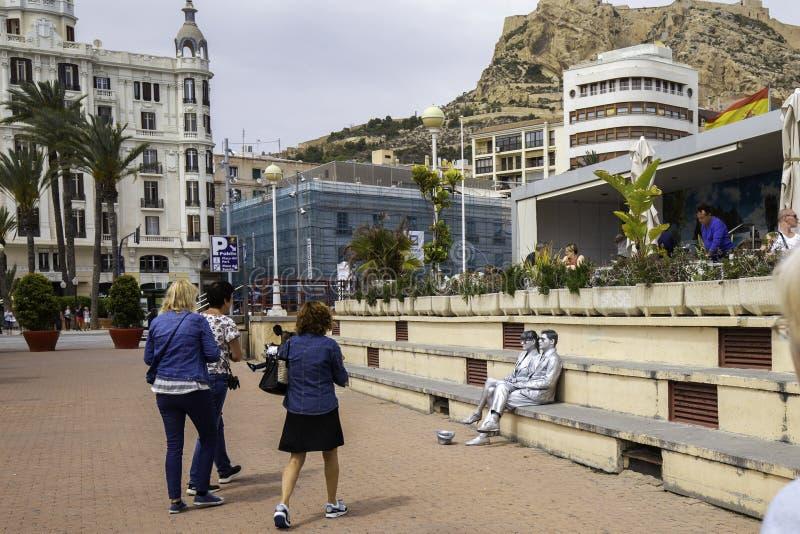 Alicante, Hiszpania Maj 06, 2018 - kobiety chodzą wzdłuż deptaka i wysyłają uliczni wykonawcy którymi z całkowicie maluje zdjęcia royalty free