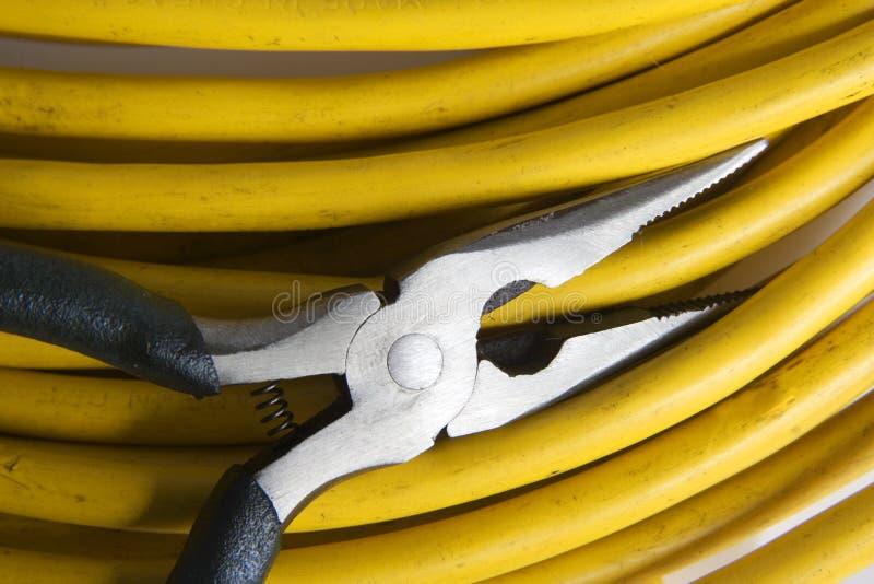 Alicates eléctricos con el cable amarillo imagenes de archivo
