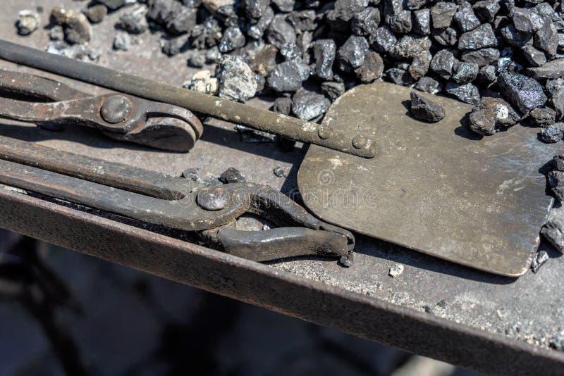 Alicates para as brasas e a pá para o carvão de uma forja medieval imagens de stock royalty free