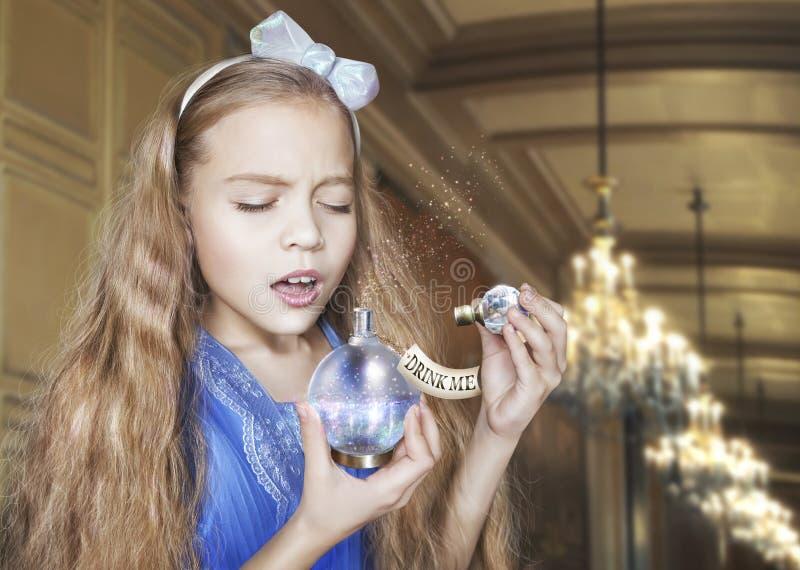 Alice in den Märchenlandgetränken von der Flasche mit den Wörtern 'trinken mich ' stockbilder