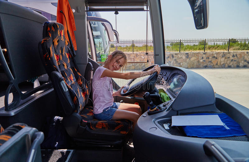 Alice drives the bus. The girl Alice drives the excursion bus and smiles stock photography