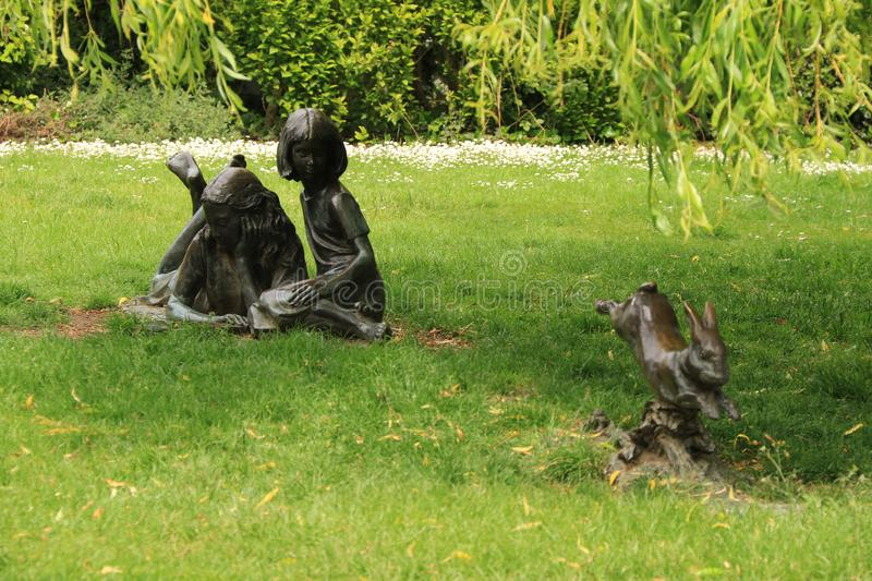 Alice and her sister. The statue of Alice and her sister watching the rabbit disappear down the rabbit hole is in Millmead, near the River Wey royalty free stock photography