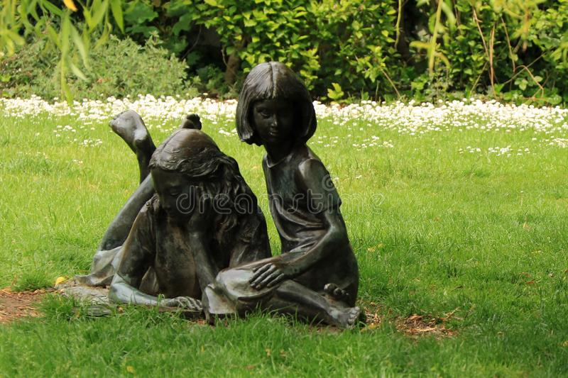 Alice and her sister. The statue of Alice and her sister watching the rabbit disappear down the rabbit hole is in Millmead, near the River Wey royalty free stock photos