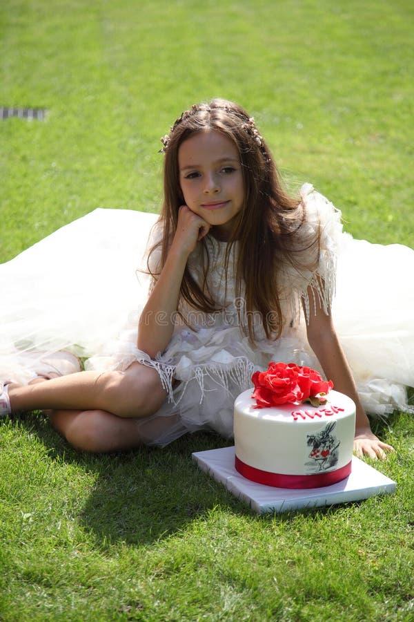 Alice pequena está sentando-se na grama Alice e bolo foto de stock