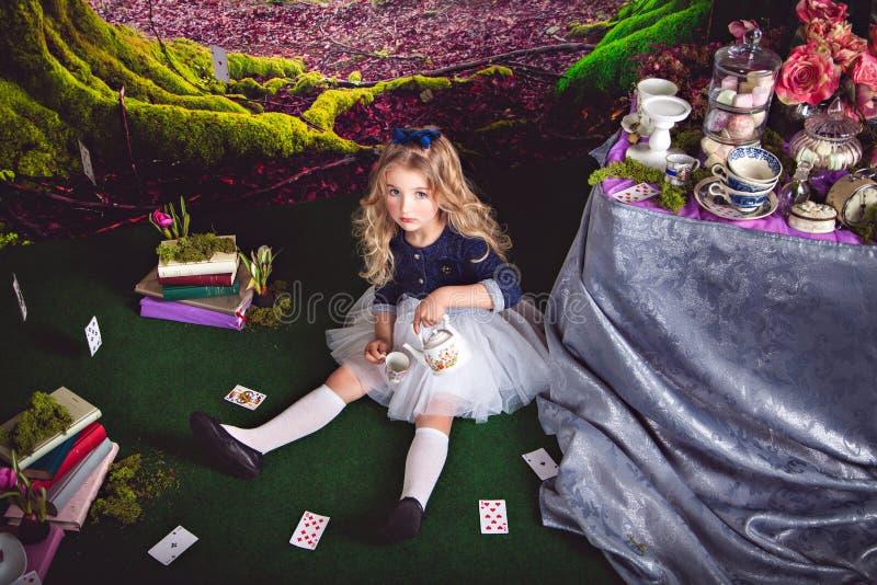 Alice pequena no chá de derramamento do país das maravilhas fotos de stock royalty free