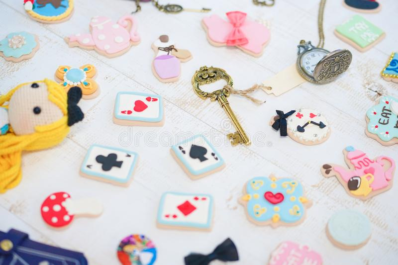 Alice`s adventure in wonderland cookies with vintage keychain and pocket watch. Soft focus on the vintage key stock image
