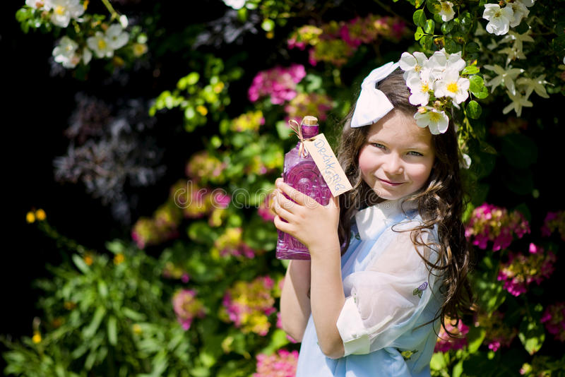 Alice in Wonderland. Recreating of Alice in Wonderland. The girl is in the garden enjoying with a bottle ~drink me stock images
