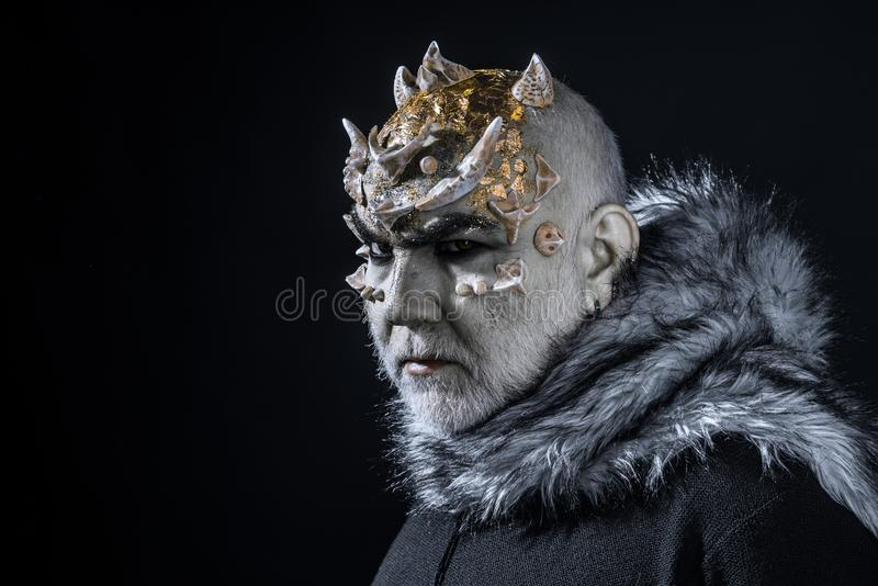 Alien, demon, sorcerer makeup. Demon on black background, copy space. Man with thorns or warts in fur coat. Theatrical royalty free stock image