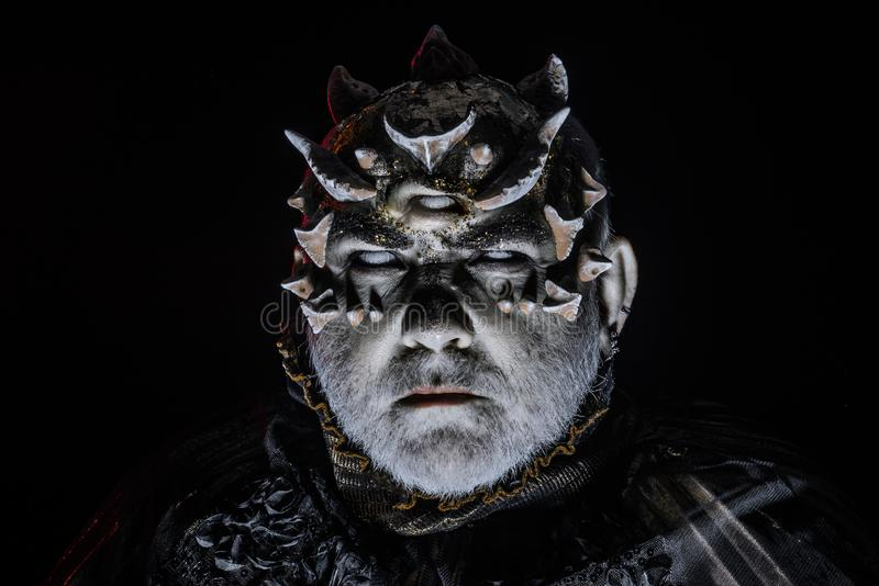 Alien, demon, sorcerer makeup. Horror and fantasy concept. Man with third eye, thorns or warts. Demon on black. Background, close up. Senior man with white royalty free stock photo