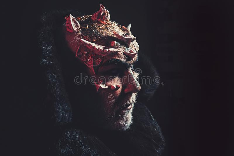 Alien, demon, sorcerer makeup. Horror and fantasy concept. Man with thorns or warts. Demon on black background, copy. Space. Senior man with white beard dressed stock images