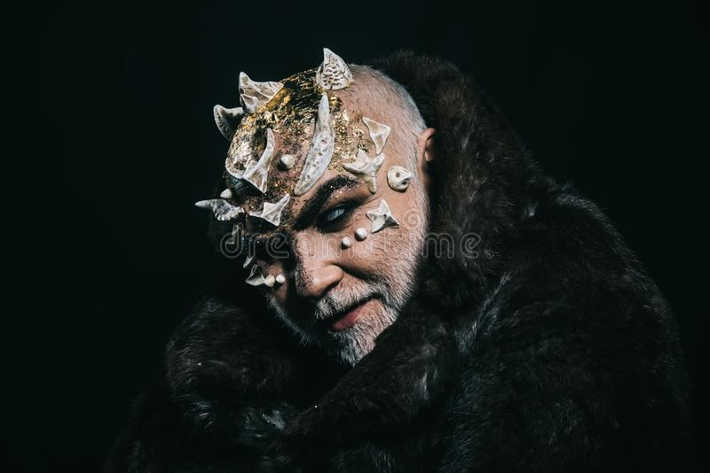 Alien, demon, sorcerer makeup. Horror and fantasy concept. Man with thorns or warts in fur coat. Demon on black. Background, copy space. Senior man with white stock images