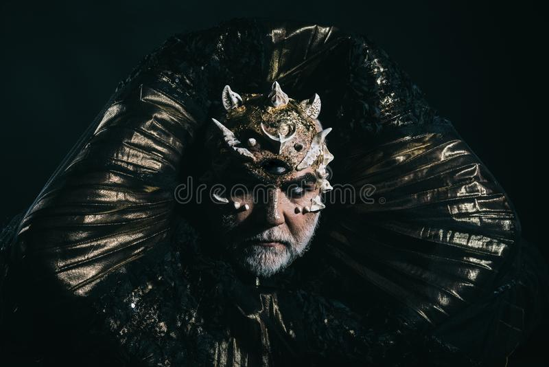 Alien, demon, sorcerer makeup. Man with third eye, thorns or warts. Demon with golden collar on black background. Horror. And fantasy concept. Senior man with royalty free stock photo