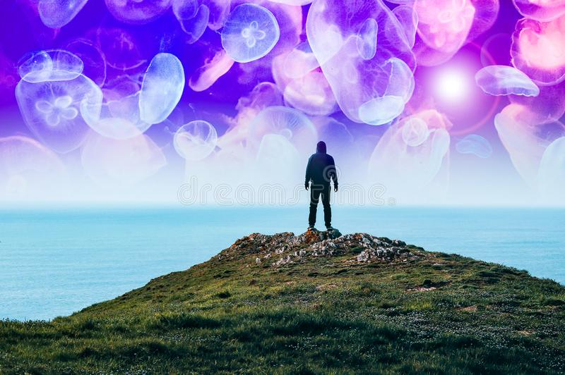 A alien dream concept. A silhouette of a hooded figure standing on a hill near the sea with glowing neon jellyfish floating in the royalty free stock image