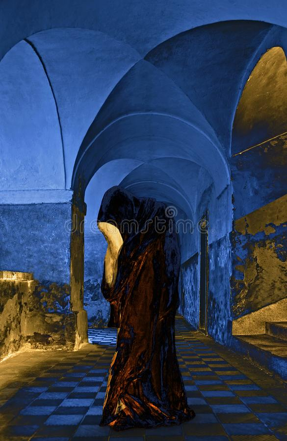 Alien - Hooded Figure Alien Looks To The Future. Hooded Figure in the castle without faces. The light comes out of the face of Hooded Figure stock image