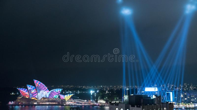 Alien Invasion Sydney Harbour. Light beams shining in the sky looking like aliens visiting earth with the Sydney Opera House being covered in bright, fluorescent royalty free stock image