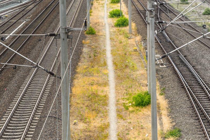 Alienujący wizerunek footpath bieg między dwa kolejowymi śladami dla pociągów obraz royalty free