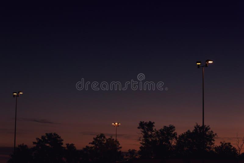 Aligere las lámparas de calle en la luz de la puesta del sol imagenes de archivo