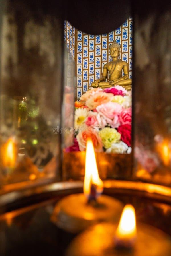 Aligere las velas y las flores coloridas hermosas para adorar de oro imágenes de archivo libres de regalías