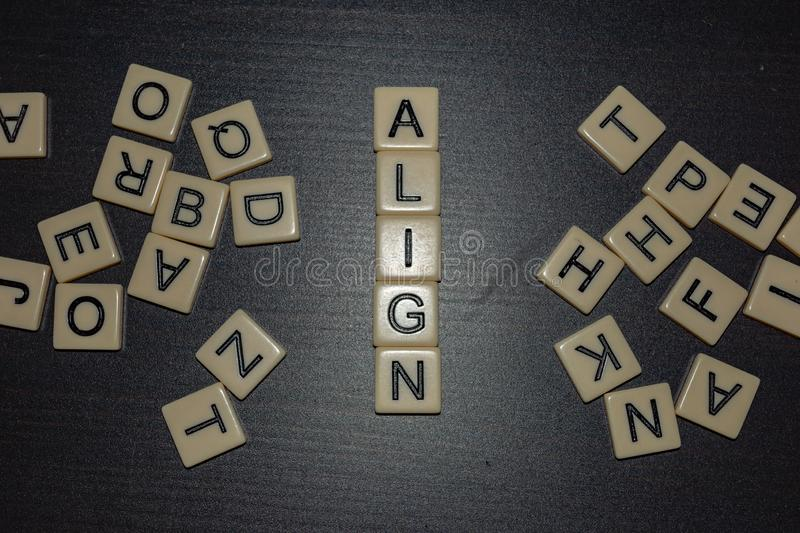 Align tile letters on black background with mixed letters on either side. Concept for business, personal or other goal-setting i. Align tile letters on a black royalty free stock image