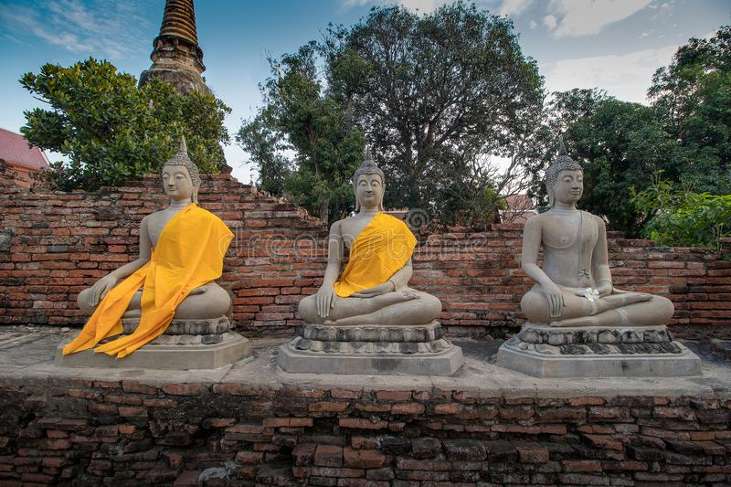 The Pagoda and Buddha Status at Wat Yai Chaimongkol, Ayutthaya,. Aligned Sitting Buddha Statues and Buddha Status at Wat Yai Chaimongkol, Ayutthaya, Thailand royalty free stock photography