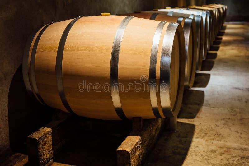 Aligned wine barrels in a cellar. Wine maturing in oak barrels in a cellar stock photography