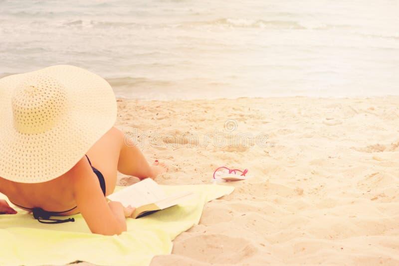 """Alikanas,扎金索斯州海岛,希腊†""""2017年9月28日:有帽子的美丽的妇女享用太阳和好书在美丽的海滩的 免版税库存图片"""