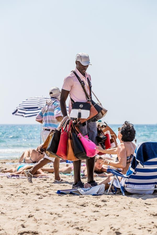 Alikante, Spanien 4. Juni 2016: Ein illegaler Einwanderer von Afrika verkauft gefälschte Taschen in Spanien stockfoto