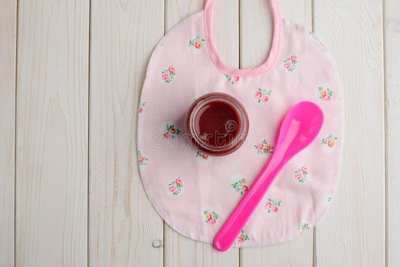 Aliment pour bébé, cuillère et bavoir images libres de droits
