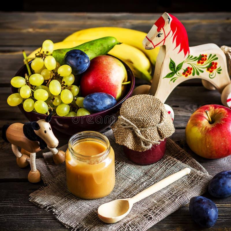 Aliment pour bébé, fruits et jouet sur la table en bois photographie stock