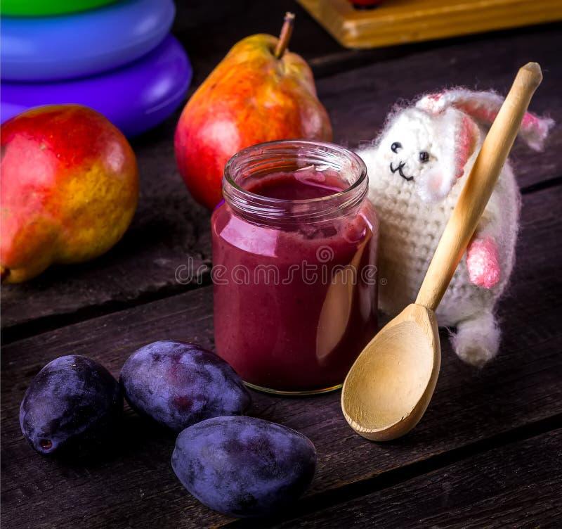 Aliment pour bébé, fruits et lapin sur la table en bois images stock