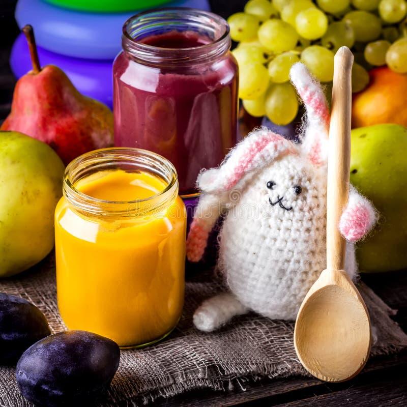Aliment pour bébé, fruits et lapin sur la table en bois image stock