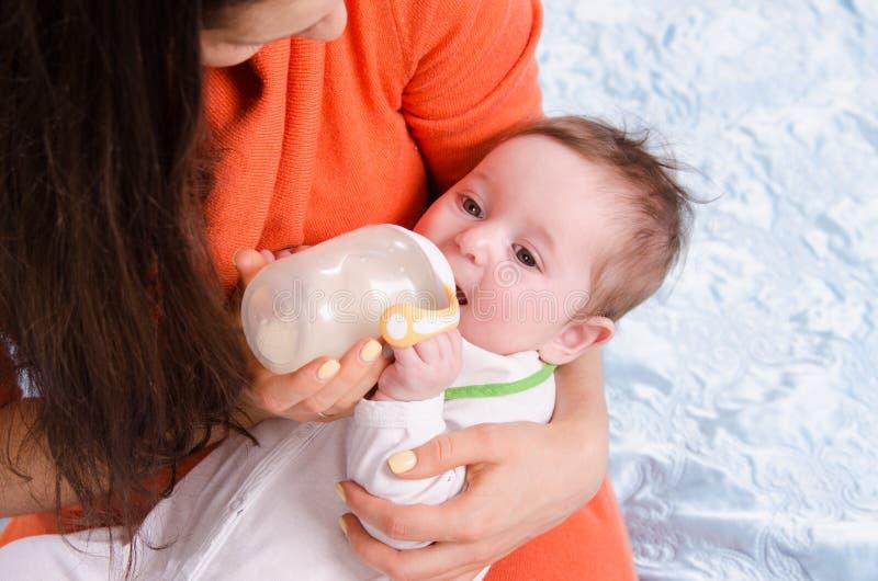 Alimentações do Mum de um bebê de seis meses da garrafa imagens de stock