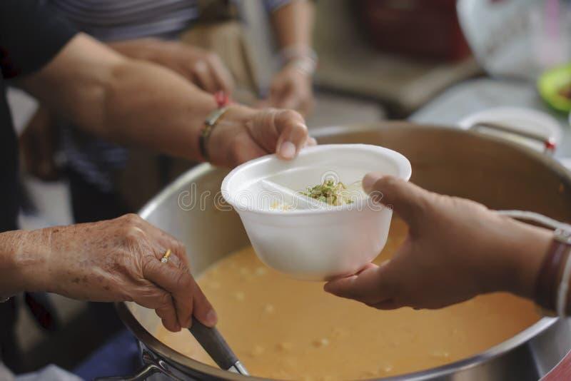 Alimentación de los pobres a las manos de un mendigo Concepto de la pobreza fotos de archivo