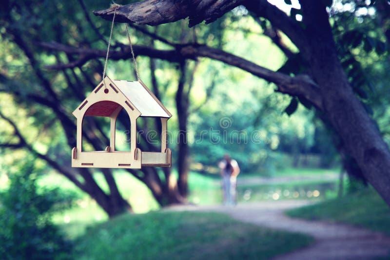 Alimentador de la forma de la pequeña casa que cuelga en la sombra del árbol, trayectoria de bosque borrosa, par romántico fotografía de archivo libre de regalías
