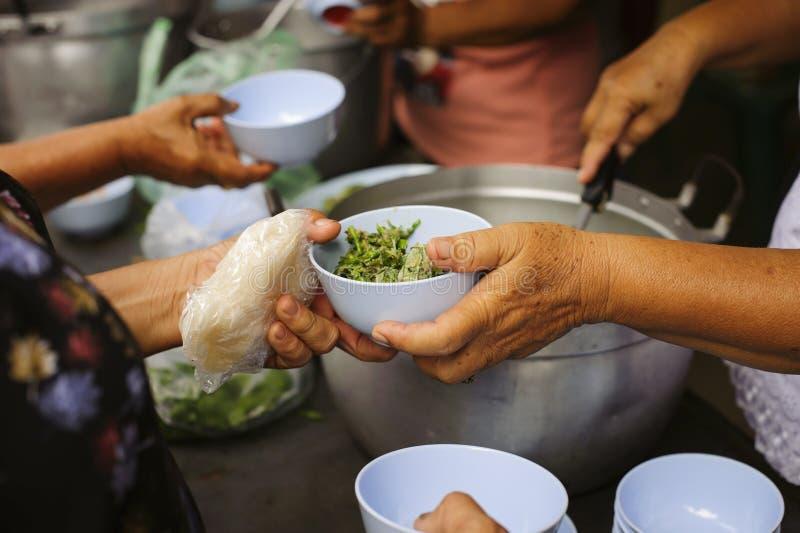 Alimentando os pobres às mãos de um mendigo: Conceito da fome e da desigualdade social: alimento de alimentação para o conceito d fotografia de stock royalty free