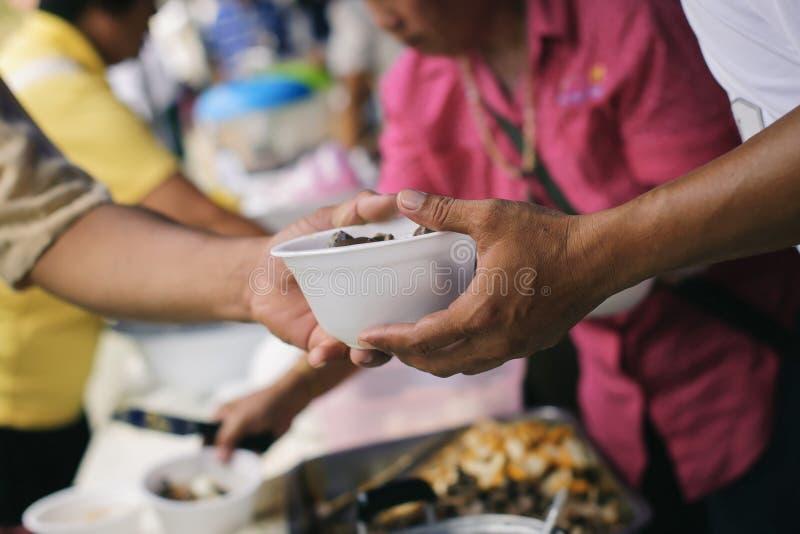 Alimentando os pobres às mãos de um mendigo: Conceito da fome e da desigualdade social: alimento de alimentação para o conceito d imagens de stock