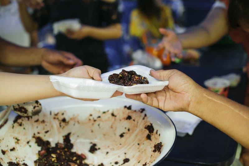 Alimentando os pobres às mãos de um mendigo: Conceito da fome e da desigualdade social: alimento de alimentação para o conceito d foto de stock royalty free