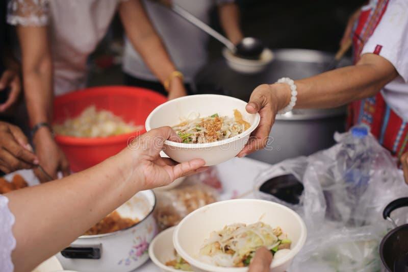 Alimentando os pobres às mãos de um mendigo: Conceito da fome e da desigualdade social: alimento de alimentação para o conceito d foto de stock