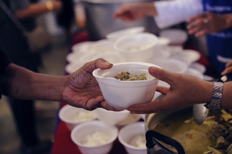 Alimentando os pobres às mãos de um mendigo Conceito da pobreza imagens de stock royalty free