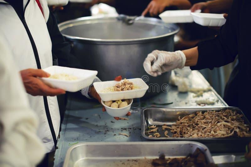 Alimentando os pobres às mãos de um mendigo Conceito da pobreza fotografia de stock royalty free