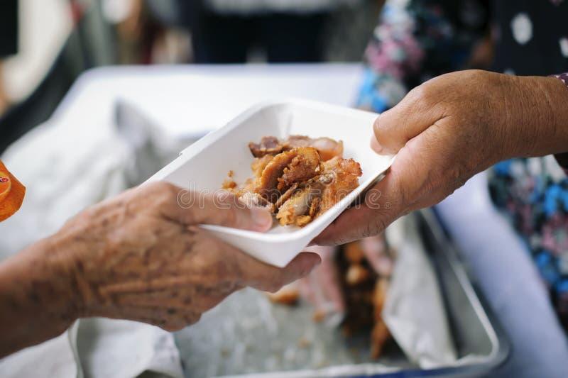 Alimentation des pauvres aux mains d'un mendiant : Concept de la famine et de l'inégalité sociale : nourriture de alimentation po photos stock
