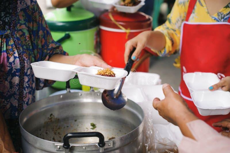Alimentation des pauvres aux mains d'un mendiant : Concept de la famine et de l'inégalité sociale : nourriture de alimentation po images libres de droits