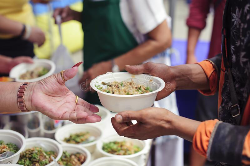 Alimentation des pauvres aux mains d'un mendiant : Concept de la famine et de l'inégalité sociale : nourriture de alimentation po photos libres de droits