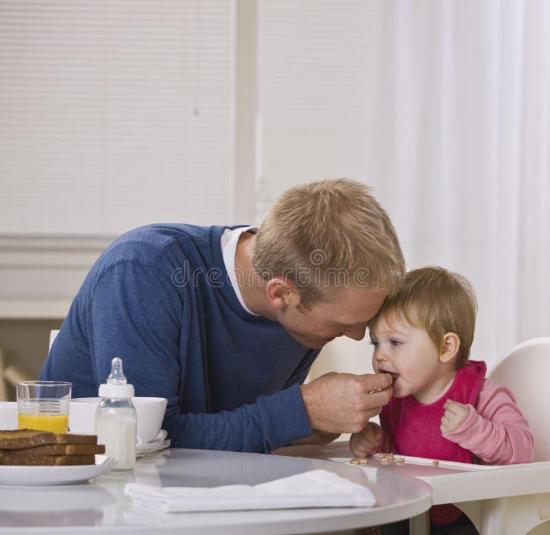 alimentazione della figlia del papà della prima colazione fotografie stock libere da diritti