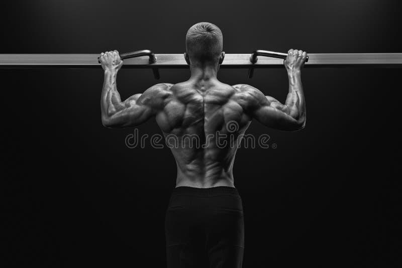 Alimenti il tipo muscolare del culturista che fa i pullups in palestra Uomo di forma fisica immagine stock libera da diritti